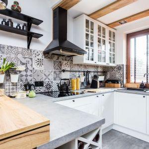 Ściana nad blatem w kuchni wykończona została patchoworkowymi płytkami w szarym kolorze. Projekt: Agnieszka Hincz. Fot. Michał Młynarczyk