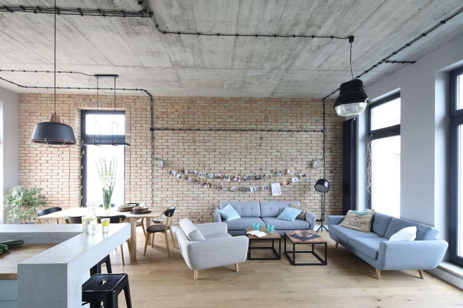 Całą ścianę w dużym, przestronnym salonie wykończono cegłą w jasnym, brązowym kolorze. Projekt: Maciejka Peszyńska-Drews. Fot. Bartosz Jarosz
