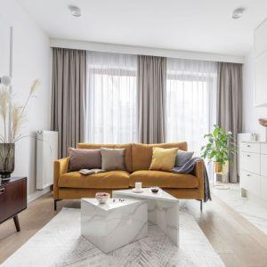 Miodowa ciepła w kolorze kanapa idealnie ożywia jasny salon. Projekt: Katarzyna Szostakowska, Kate&Co. Fot. Marta Behling z PionPoziom