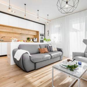 Prosta szara sofa zestawiona z bielą, beżem i naturalną drewnianą podłogą. Projekt: Joanna Nawrocka, JN Studio Joanna Nawrocka. Fot. Łukasz Bera