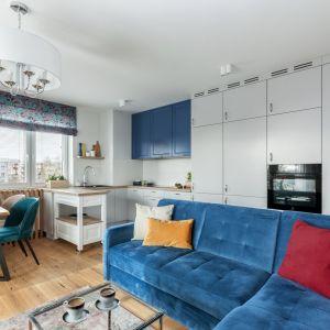 Mocny akcent w salonie - niebieska kanapa - dobrze wygląda na białym tle i z jasną drewnianą podłogą. Projekt: Justyna Mojżyk, poliFORMA. Fot. Monika Filipiuk-Obałek