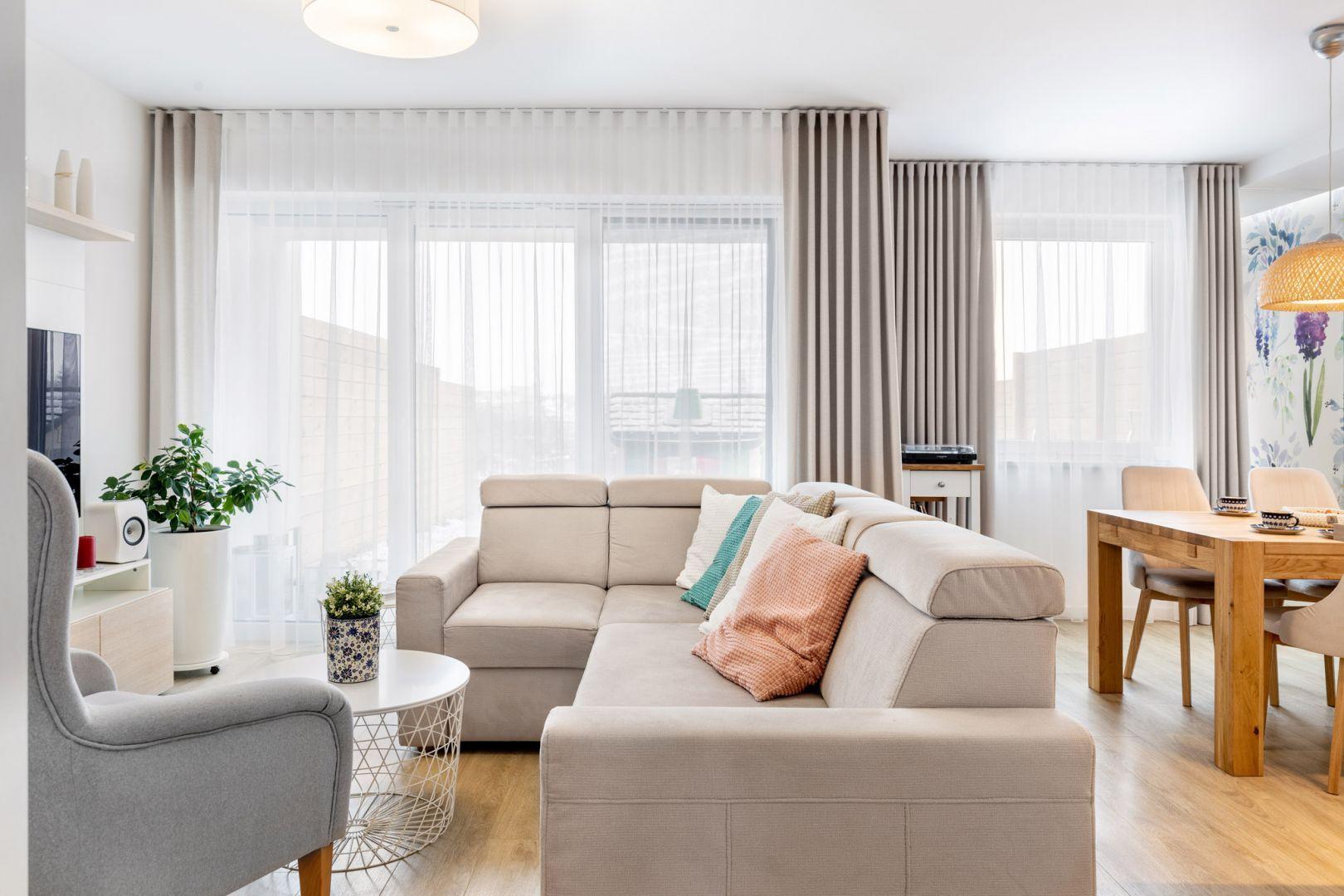 Beżowa sofa, podłoga w kolorze drewna i pastelowe dodatki w salonie. Projekt: Joanna Nawrocka, JN Studio Joanna Nawrocka. Fot. Łukasz Bera