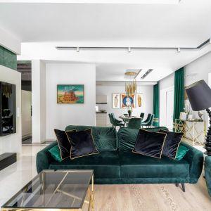 Kanapa w kolorze butelkowej zieleni, ściany w podobnym odcieniu i bardzo jasna podłoga. Projekt: Trędowska Design. Fot Michał Bachulski