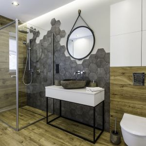 Łazienkę z prysznicem urządzono nowocześnie. Biel i szarości świetnie ocieplają płytki imitujące drewno. Projekt: Dominika Jurczak, DK architektura wnętrz. Fot. Krzysztof Czapor