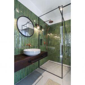 Nowoczesna łazienka z prysznicem wykończona jest lśniącymi płytkami w zielonym kolorze. Nietypowa okładzina świetnie koresponduje z czernią profili kabiny prysznicowej i ciemnym drewnem szafki podumywalkowej. Projekt: Plan 9. Studio architektury. Katarzyna Kaftańska. Fot. Tomasz Hejna LAGOMphoto