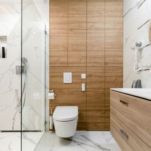 W nowoczesne łazience z prysznicem postawiono na biel z rysunkiem marmuru oraz drewno, które świetni ociepla przestrzeń. Projekt i zdjęcia: Monika Staniec