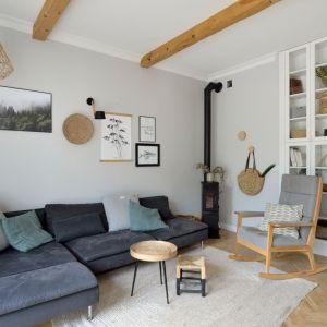 Jasny, przytulny salon. Szare ściany świetnie pasują do drewnianej podłogi. Mocniejszym elementem jest tu kanapa. Projekt: SHOKO.design. Fot. Łukasz Nowosadzki