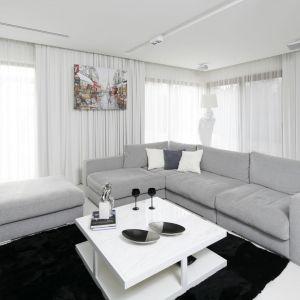 Jasny salon urządzony jest w kolorze białym i szarym. Czarne dodatki pięknie dopełniają aranżację. Projekt: Małgorzata Muc, Joanna Scott. Fot. Bartosz Jarosz