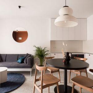 Nowoczesna, prosta biała kuchnia i równie nowoczesny salon. Projekt: pracownia 3XEL. Fot. Dariusz Jarząbek