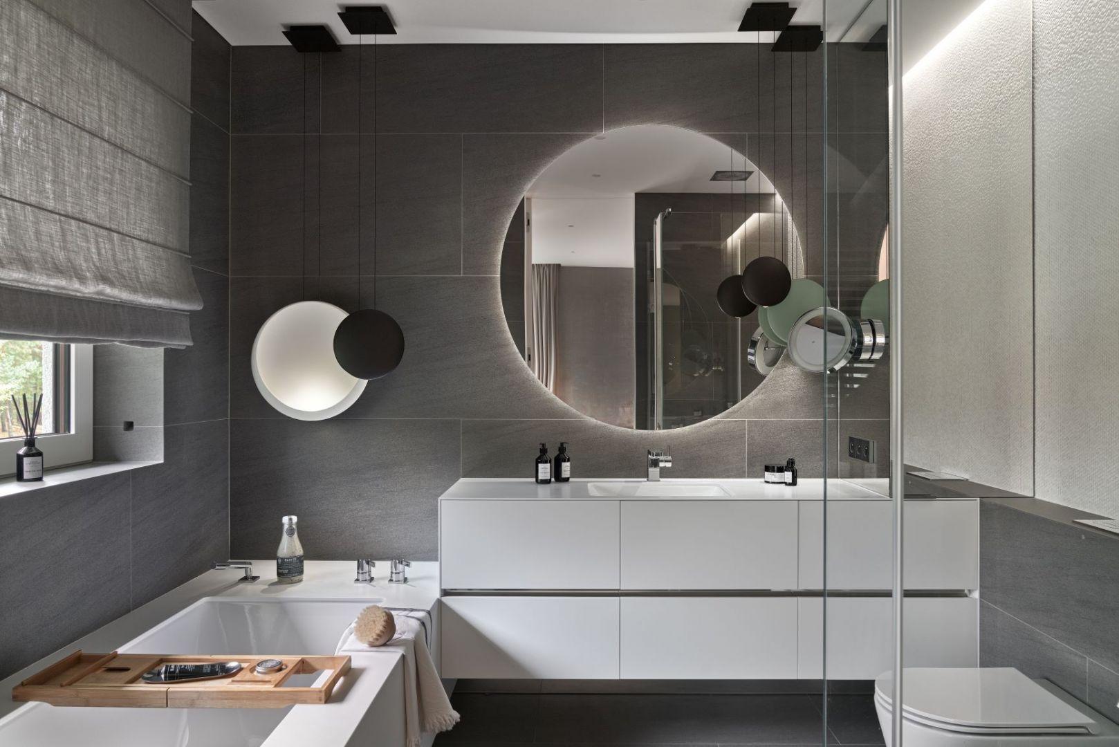 Okrągłe lustro w nowoczesnej łazience urządzone w szarej kolorystce. Projekt: Katarzyna Kraszewska Architektura Wnętrz. Fot. Tom Kurek