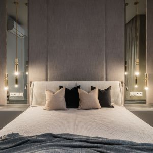 Ścianę za łóżkiem w sypialni wykończona jest tapicerowanym zagłówkiem oraz pionowymi lustrami, w których odbijają się zwieszające się z sufitu złociste lampy Fulcrum projektu Lee Brooma. Projekt: Katarzyna Kraszewska Architektura Wnętrz. Fot. Nate Cook Photography