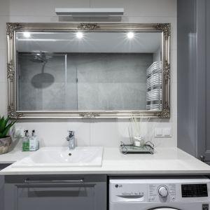 Duże lustro w dekoracyjne, srebrnej rami prezentuje się bardzo stylowo w jasnej łazience. Projekt: Justyna Mojżyk, poliFORMA. Fot. Monika Filipiuk-Obałek