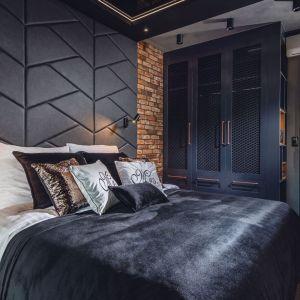 Ściana za łóżkiem w sypialni wykończona jest czarnymi,  tapicerowanymi panelami i piękną, naturalną cegłą. Projekt: Agnieszka Hajdas-Obajtek. Fot. Wojciech Kic