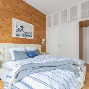 Ściana za łóżkiem w sypialni wykończona jest jasnym drewnem. Projekt: EMC Partners Ewa Mroczek - Chojecka, Paulina Kobylarz. Fot. Pion Poziom