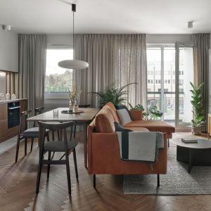 Salon z kuchnią i jadalnią urządzono inspirując się designem lat 50-tych i stylem mid-century. Projekt: Raca Architekci. Fot. Tom Kurek
