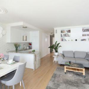 Biały salon połączony z kuchnią i jadalnią ociepla jasna, drewniana podłoga. Projekt: Laura Sulzik. Fot. Bartosz Jarosz