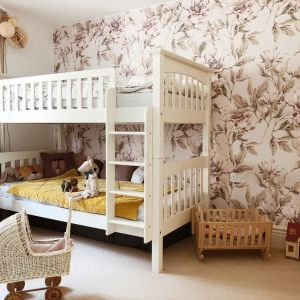 Ściany w pokoju dziecka wykończone tapetą w kwiatowy wzorze. Fot. Dekornik