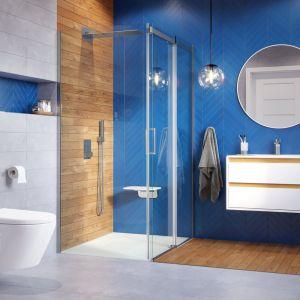 Przepiękna łazienka w kolorze niebieskim i z rysunkiem drewna. Na zdjęciu głowica prysznicowa ścienna z funkcją kaskady, kabina seria Rols, brodzik seria Lavano. Fot. Excellent