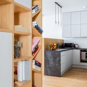 Cała zabudowa, podobnie jak reszta mieszkania, jest utrzymana w szaro-dębowej kolorystyce. Projekt Modify. Fot. Michał Młynarczyk