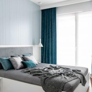 Ściana za łóżkiem w sypialni wykończona jest panelami w niebieskim kolorze oraz lakierowanym mdf-ie w białym kolorze. Projekt: Anna Maria Sokołowska. Fot. Katarzyna Seliga-Wróblewska, Marcin Wróblewski/Fotomohito