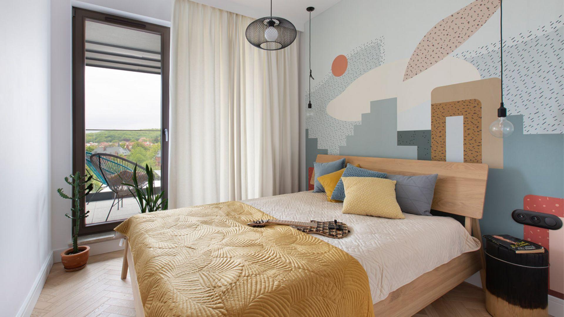 Ściana za łóżkiem w sypialni wykończona jest kolorową tapetą o ładnym, geometrycznym wzorze. Kolory są subtelne i spokojne. Projekt: Marta Kodrzycka, Marta Wróbel, Grupa Malaga. Fot. Magdalena Łojewska