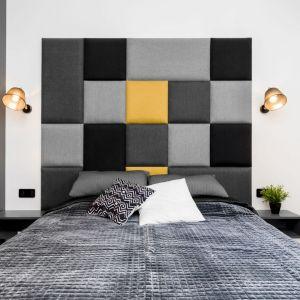 Ściana za łóżkiem w sypialni wykończona jest tapicerowanym zagłówkiem w trzech kolorach: szarym, czarnym i żółtym. Kolor żółty pięknie ożywia kompozycję kwadratów na ścianie. Projekt: Joanna Nawrocka, JN Studio Joanna Nawrocka. Fot. Łukasz Bera