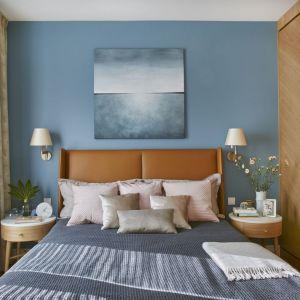 Ściana za łóżkiem w sypialni wykończona jest farbą w kolorze zgaszonego błękitu. Projekt: Joanna Kiryłowicz. Fot. Celestyna Król