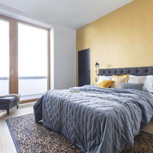 Ściana za łóżkiem w sypialni wykończona jest farbą w słoneczny, żółtym kolorze. Projekt: Renee's Interior Design Fot. Marta Behling Pion Poziom - Fotografia Wnętrz