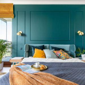 Ściana za łóżkiem w sypialni wykończona jest sztukaterią pomalowaną farbą w głębokim kolorze morza. Projekt: Joanna Rej. Fot. Pion Poziom