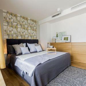 Ściana za łóżkiem w sypialni wykończona jest kolorową tapetą. Projekt: TWORZYWO studio i Paulina Kałużna. Fot. Jacek Gadaj