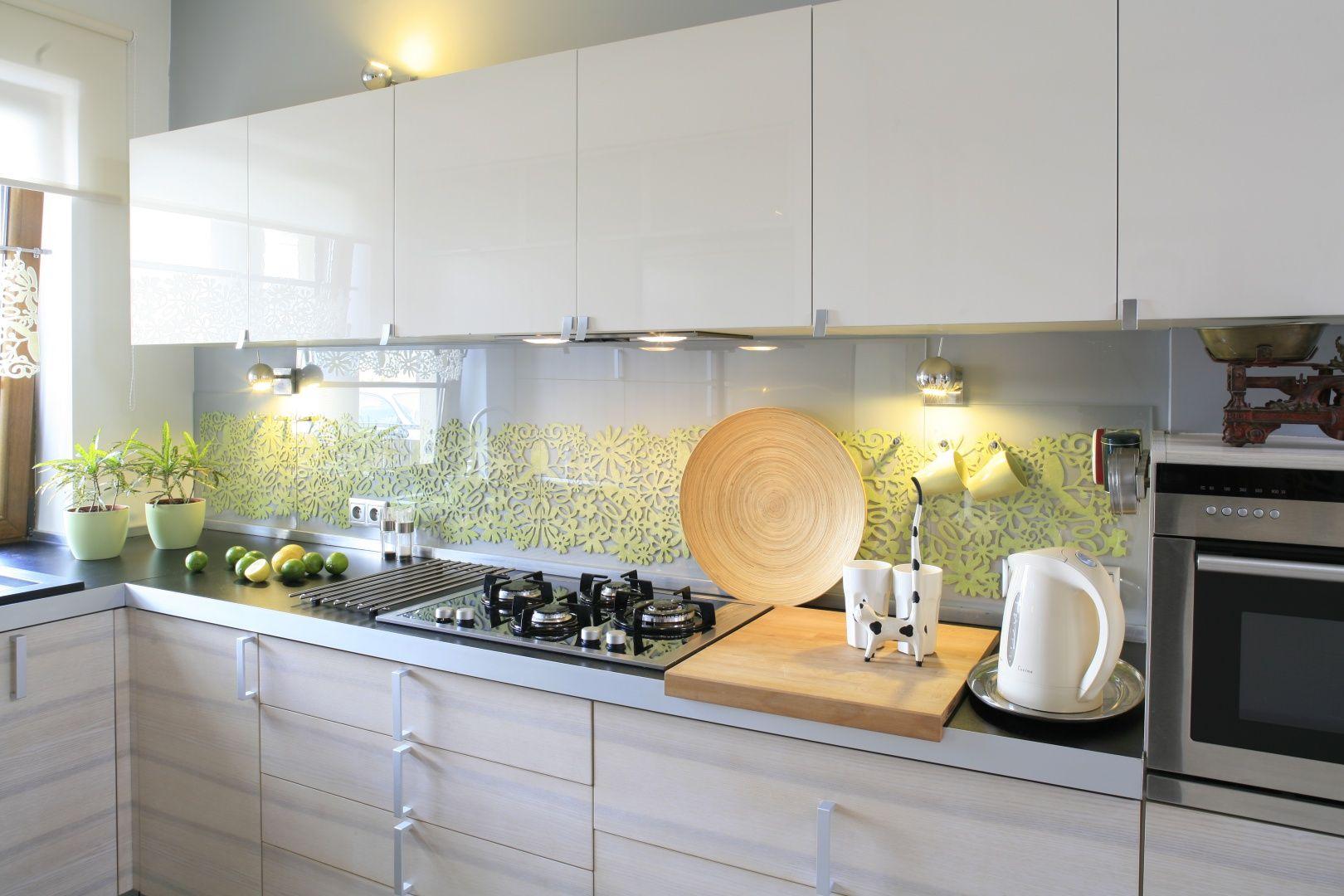 Ściana nad blatem w kuchni wykończona jest szarą farbą i  dodatkowo udekorowana wzorami z zielonego filcu. Całość osłonięto przeźroczystym szkłem. Projekt: Marta Kruk. Fot. Bartosz Jarosz