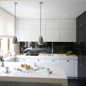 Ściana nad blatem w kuchni wykończona jest szkłem w czarnym kolorze. Projekt: Łukasz Sałek. Fot. Bartosz Jarosz