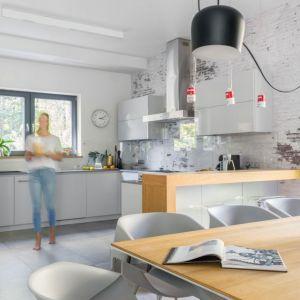 Ściana nad blatem w kuchni wykończona jest tapetą imitującą cegłą i zabezpieczona bezbarwnym szkłem. Projekt: Małgorzata Denst. Fot. Pion Poziom