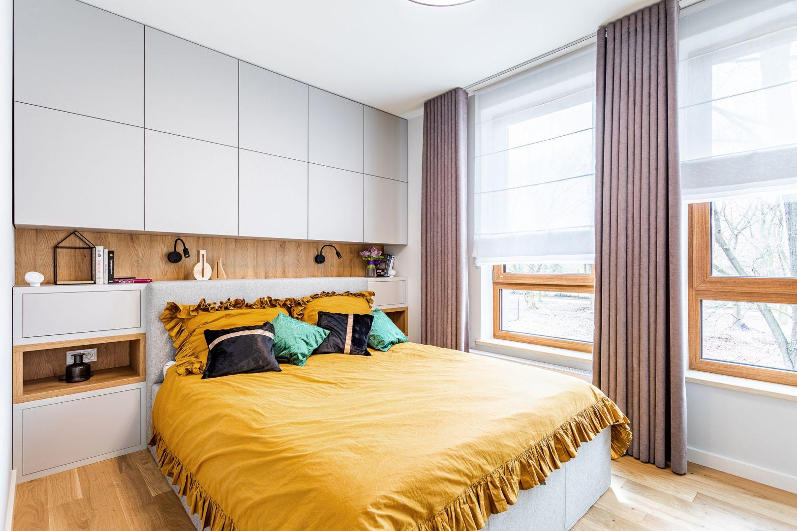 Jasna sypialnia urządzona została w delikatnych szarościach, które ociepla piękne wybranianie drewna. Projekt: Modify. Fot. Michał Młynarczyk