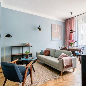 Oświetlenie i regały w salonie wprowadzają też nieco loftowy klimat. Projekt i stylizacja wnętrza: Ola Dąbrówka, pracownia Good Vibes Interiors. Zdjęcia: Marcin Mularczyk