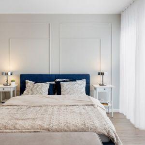 Jasna sypialnia z dużym, tapicerowanym łóżkiem w ciemnym niebieskim kolorze. Projekt: Joanna Nawrocka, JN Studio Joanna Nawrocka. Fot. Łukasz Bera