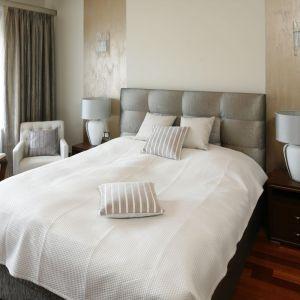 Jasna sypialnia urządzona w przytulnych beżach. Połyskujące powierzchnie czy stylizowane lampy tonuje neutralna paleta barw. Projekt: Kinga Śliwa. Fot. Bartosz Jarosz