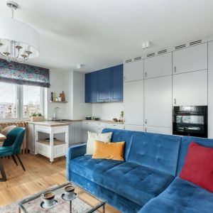 Kolor w kuchni. Niebieska kanapa idealnie pasuje do wiszących szafek w kuchni. Projekt: Justyna Mojżyk, poliFORMA. Fot. Monika Filipiuk-Obałek
