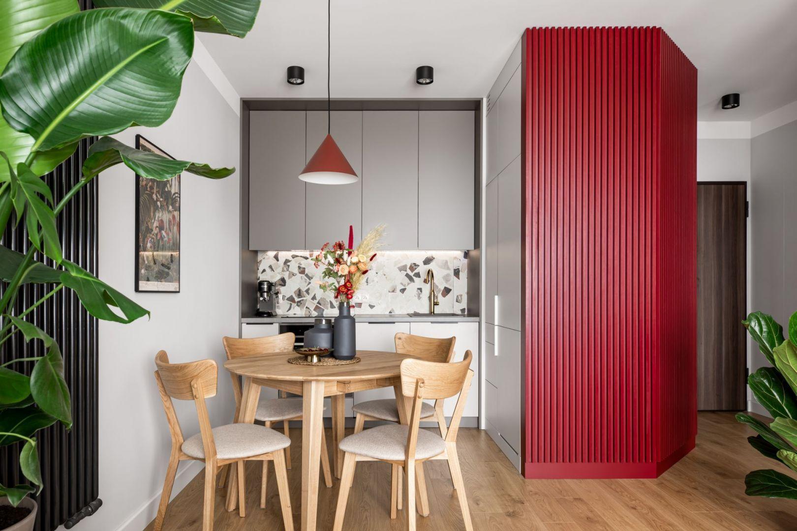 Kolor w kuchni. Elementy w czerwonym kolorze ożywiają niedużą kuchnię połączoną z jadalnią. Projekt: Maria Nielubszyc, pracownia PURA design. Fot. Jakub Nanowski