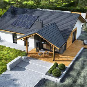 Dom Mini 4 w. II do strony ogrodu zachwyca dekoracyjnym tarasem z klimatycznym kominkiem zewnętrznym. Projekt: pracownia Archipelag