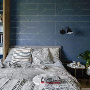 Ściana za łóżkiem w sypialni wykończona jest ciemną, niebieską tapetą o delikatnym geometrycznym wzorze. Projekt: Magdalena Bielicka, Maria Zrzelska-Pawlak, pracownia Magma. Fot. Kroniki Studio