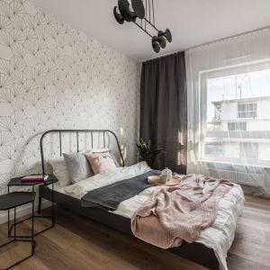 Ściana za łóżkiem w sypialni wykończona jest jasną tapeta o delikatnym wzorze. Projekt: Ewelina Matyjasik-Lewandowska. Fot. Tomasz Kazaniecki