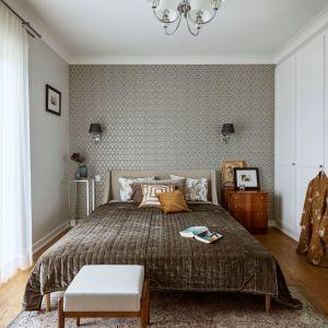 Ściana za łóżkiem w sypialni wykończona jest połyskującą tapetą o eleganckim wzorze. Projekt: Małgorzata Bacik, MM Architekci x Dekorian Home. Fot. Yassen Hristov