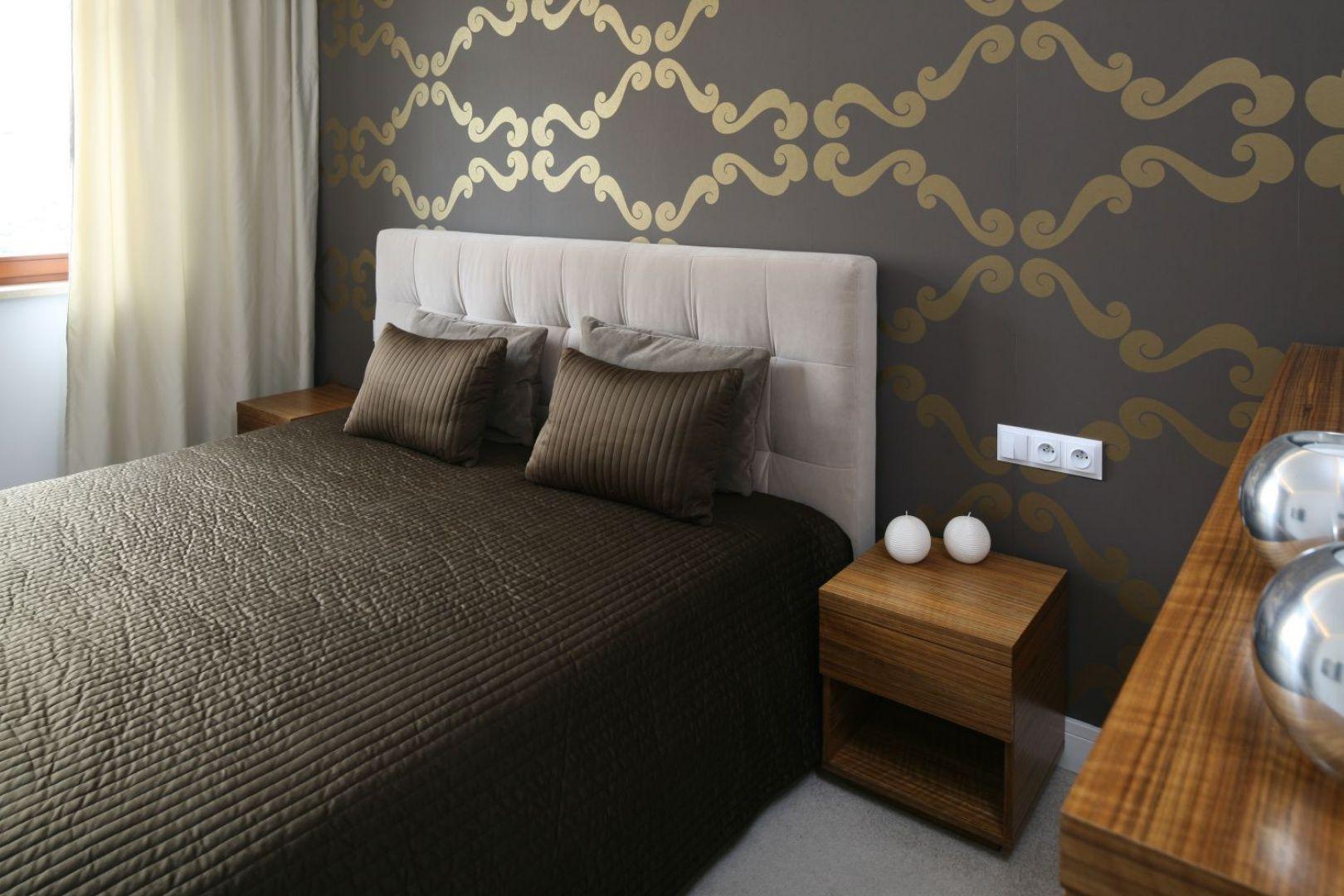 Ściana za łóżkiem w sypialni wykończona jest ciemną tapetą o złotym wzorze. Projekt: Małgorzata Galewska. Fot. Bartosz Jarosz.