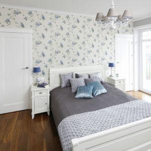 Ściana za łóżkiem w sypialni wykończona jest jasną tapeta w delikatne niebieskie kwiaty. Projekt: Maciejka Peszyńska-Drews. Fot. Bartosz Jarosz