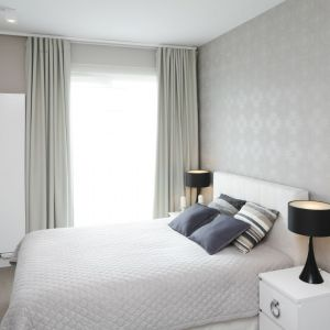 Ściana za łóżkiem w sypialni wykończona jest jasną, połyskującą tapetą o delikatnym wzorze. Projekt: Małgorzata Galewska. Fot. Bartosz Jarosz