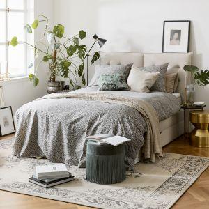 Ładna sypialnia. Beżowe tapicerowane łóżko, piękne dekoracje i dużo roślin. Pomysły na aranżację sypialni. Fot. WestwingNow