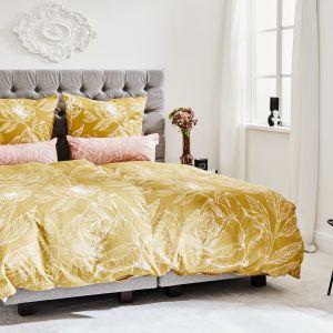 Ładna sypialnia z beżowym pikowanym łóżkiem i złotą pościelą. Pomysły na aranżację sypialni. Fot. WestwingNow