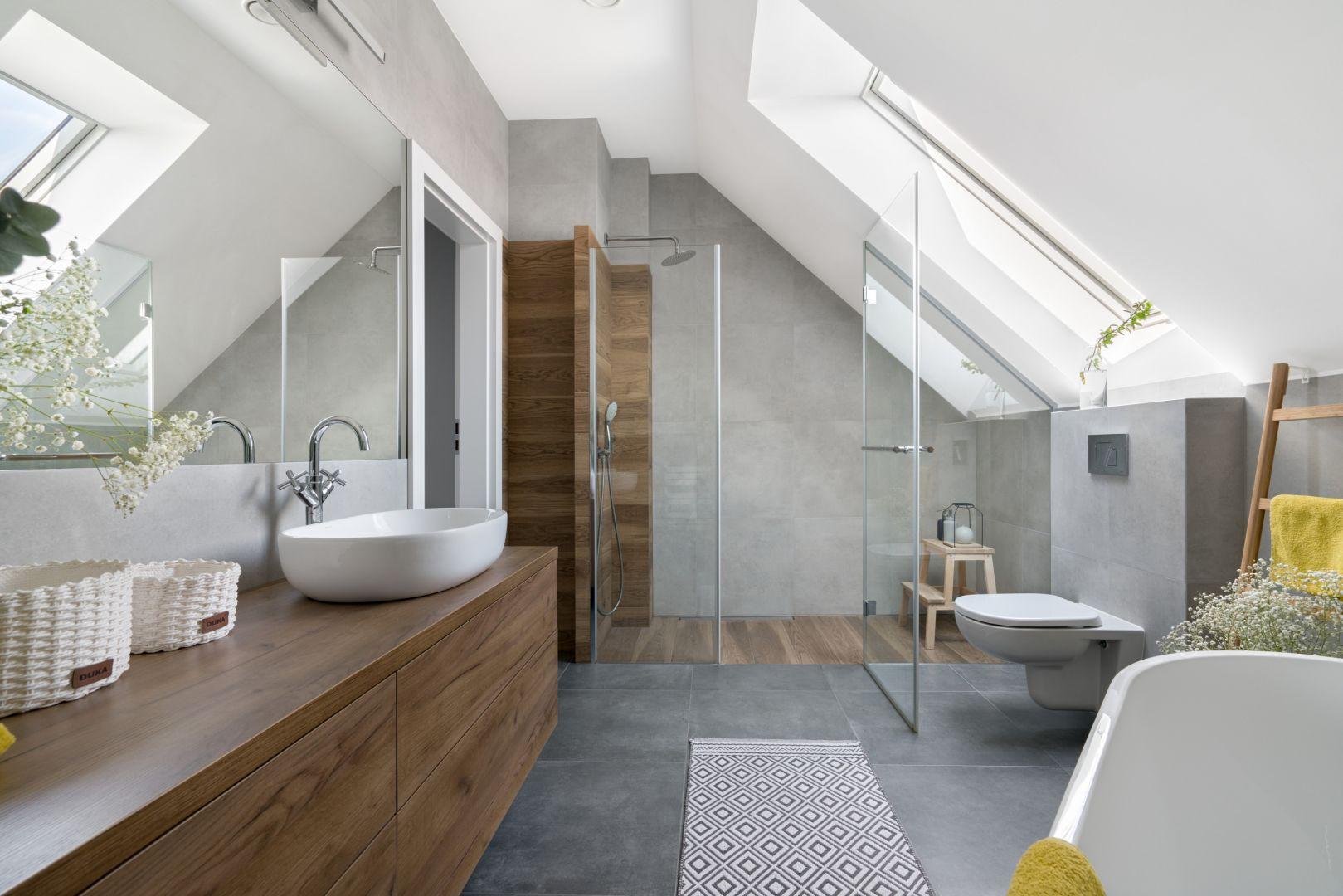 W łazience sprawdzają się szare płytki i te w kolorze drewna - najmniej widać na nich kurz i kamień. Projekt: MM Architekci. Fot. Jeremiasz Nowak