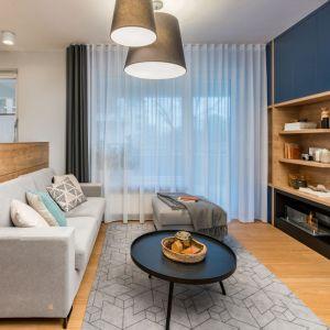 Ściana za telewizorem w salonie wykończona jest drewnem i ciemny, niebieskim kolorem. Projekt: InDe Projekt. Fot. Bartek Bieliński